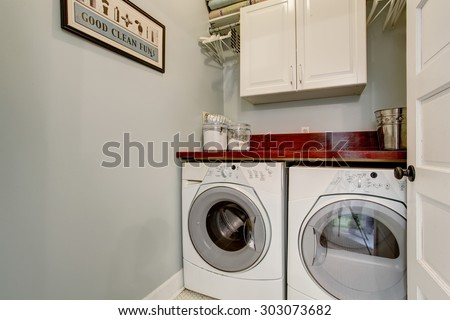Small laundry room with tile floor, door, and washer dryer set. - stock photo