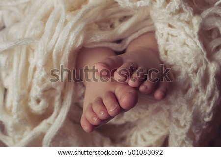 Small legs of newborn wrapped in a blanket