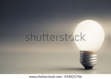 Small light bulb glowing on gray background