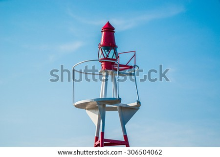 Small lighthouse on blue sky in daylight - stock photo