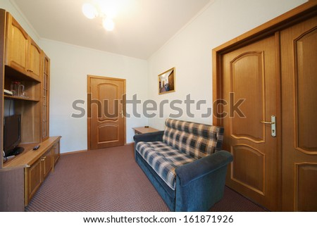 Small living room with a blue checkered sofa, wall cabinet and TV - stock photo