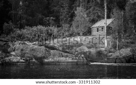 small log cabin near the water on the rock - stock photo
