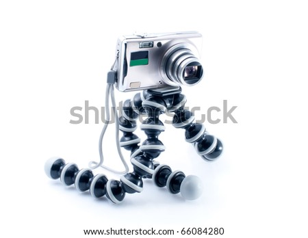 Small metal Digital photo camera and tripod  on white background - stock photo