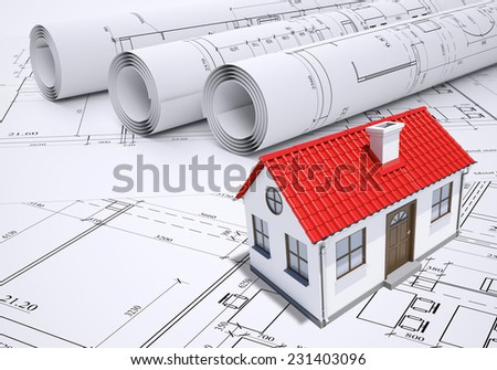 Small model house with red roof near scrolls of architectural drawings. Construction concept - stock photo