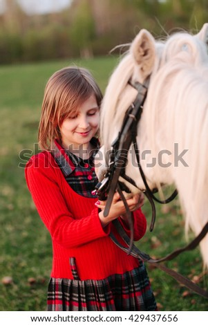 Small model of a young girl child looks at a white horse Outdoors - stock photo