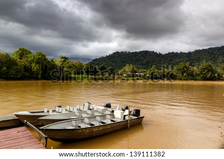 Small motor boats tied up at a small dock on a chocolate brown colored rain forest river - stock photo