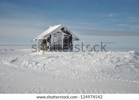 Small mountain shelter house on white snow against blue sky - stock photo