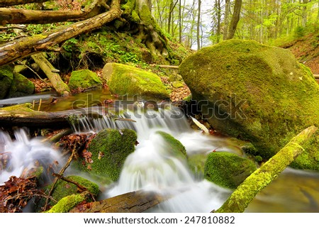 small mountain stream among green stones  - stock photo