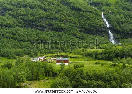 Small Mountain Village at Fjords in Flam, Norway. At summer time. The snows is melting and become waterfalls  - stock photo