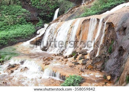 Small natural spring waterfall in a mountains surrounded by moss and grass - stock photo