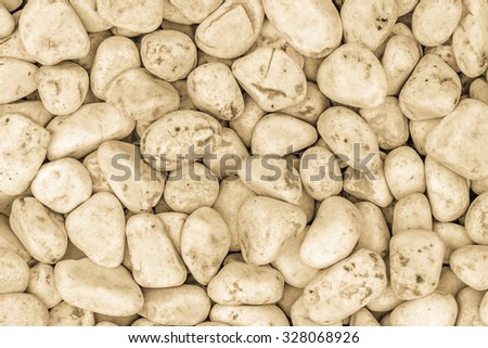 Small naturally polished white rock pebbles background in yellow / golden tone - stock photo
