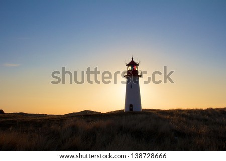 Small North Sea lighthouse shot against a clear sky at dusk with the sun creating a halo in the background