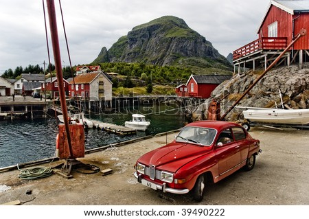 Small Norwegian fishing village - red houses, old car, small port with crane. all under majestick mountain. Lofoten islands. - stock photo