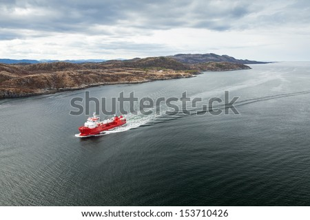 Small Norwegian red oil products tanker ship in the fjord - stock photo