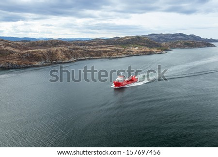 Small Norwegian red oil products tanker ship sails in the fjord - stock photo