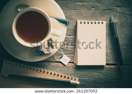 Small notepad with a cup of tea, pen and pencil on rustic wood background with film filter effect - stock photo