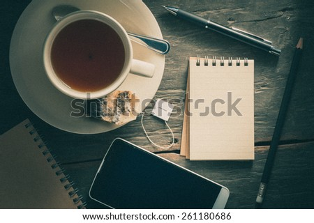 Small notepad with a cup of tea, pen, pencil and cellphne on rustic wood background with film filter effect - stock photo