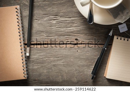 Small notepad with empty coffee cup, tea bag, pen and pencil on rustic wood background with low key scene - stock photo