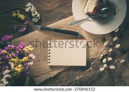 Small notepad with pen and pencil on rustic wood background with film filter effect - stock photo