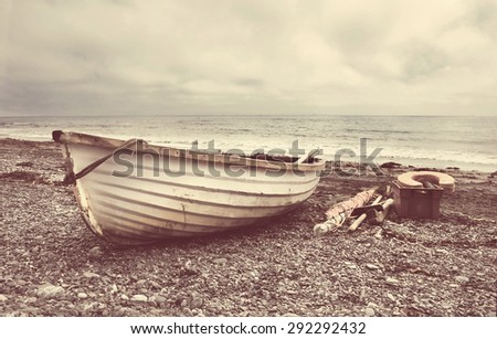 Small old fishing boat on a Cornish beach with instagram style filter - stock photo