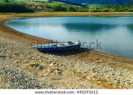 Small old fishing boat on a lake shore - stock photo