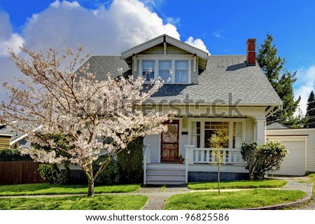 Small old white house with a blooming cherry tree and green grass. - stock photo