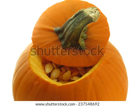 Small orange pumpkin with the top open to reveal seeds inside, on white - stock photo