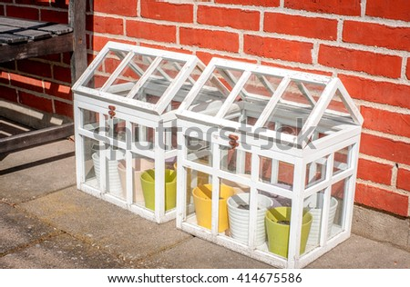 Small outdoors greenhouse in white colors at a terasse - stock photo