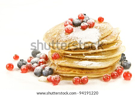 Small pancakes topped with red currants and bilberries on white background - stock photo