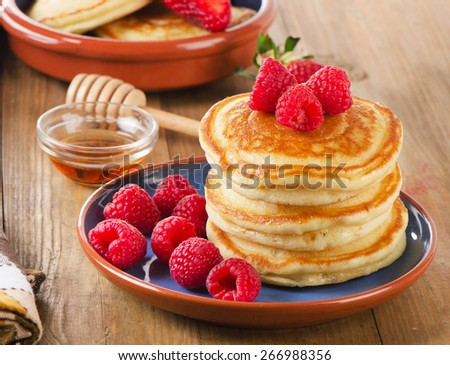 Small pancakes with fresh berries and  butter . Selective focus - stock photo