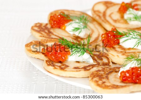 small pancakes with red caviar and sour cream - stock photo