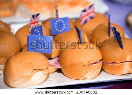 Small panini with ham and flags on a table. - stock photo