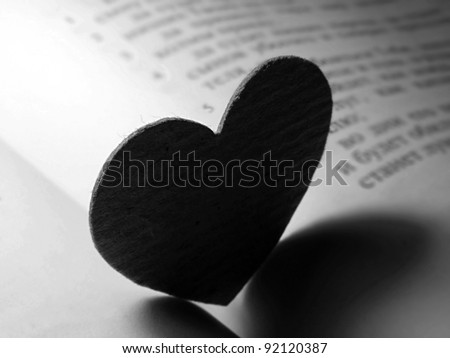 Small paper heart on a book. Black and white style. - stock photo