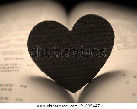 Small paper heart on a book. Sepia style. - stock photo