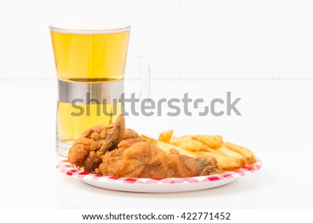 Small paper plate with pieces of southern fried chicken and french fried potatoes. - stock photo