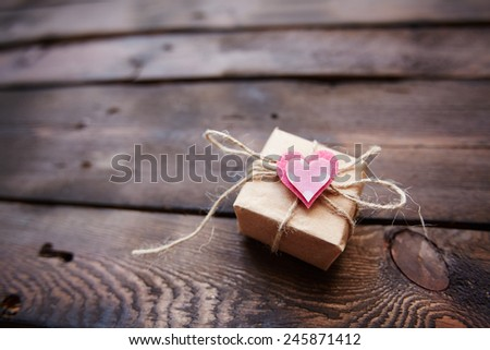 Small parcel tied up by thread with pink heart on its top