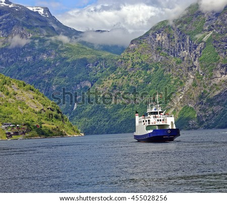 Small passenger ferry departing the village of Geiranger in the headwaters of the beautiful Geiranger Fiord in Norway