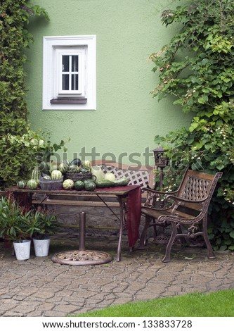 Small patio or street garden with rustic chair and table, green vegetable and plants.