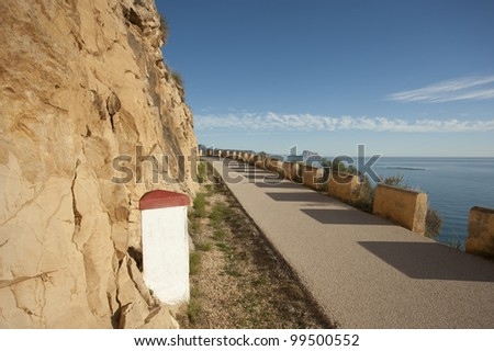 Small paved road running across a sunny landscape - stock photo