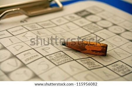 Small pencil and crossword - stock photo