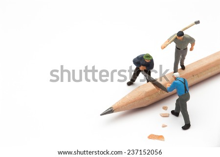Small people with handsaw cutting the pencil  - stock photo