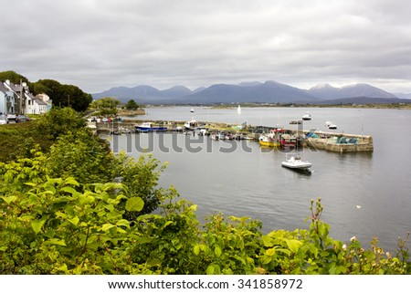 Small picturesque town in Connemara region in Western Ireland with it's bay of water and range of mountains visible over horizon  - stock photo