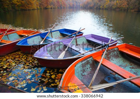 Small pier with boats on lake. Colorful autumn landscape