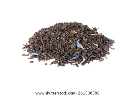 Small pile of big leaf black tea mixed with blue cornflower petals and pieces of bergamot isolated on white background, selective focus with shallow DOF - stock photo