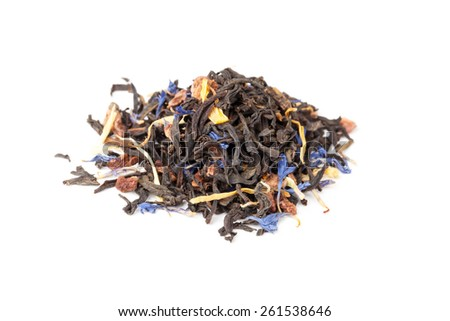 Small pile of big leaf black tea mixed with herbs and dry fruits. Calendula, sunflower, cornflower, rosehip berries. Selective focus with shallow DOF - stock photo