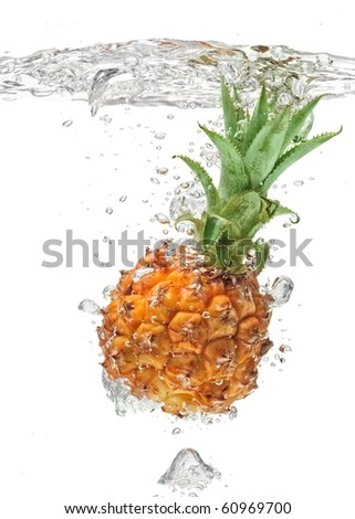 Small pineapple falling in water on white with air bubbles