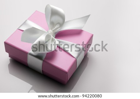 small pink box tied with a white ribbon - stock photo