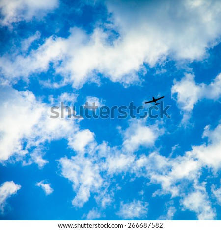 Small plan on clouds background - stock photo