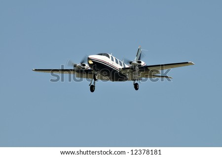 Small plane coming in for a landing against a clear sky