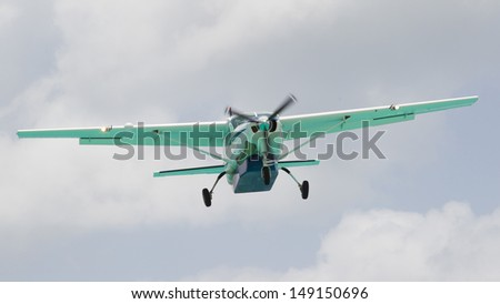 Small plane descending against a cloudy sky - stock photo
